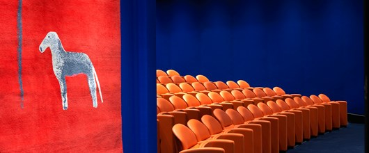 The entry to the state-of-the-art screening room with 130 comfortable leather seats in bright coral and electric blue walling.