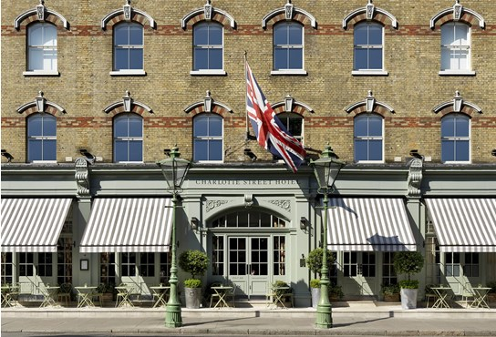 An exterior shot of the Charlotte Street Hotel face on from the other side of the street, showing outdoor terrace, olive trees at each side of the entrance doors and Union Jack blowing in the wind.