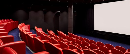 Large screening room at Soho Hotel. Tiered rows of red leather seats face towards a blank cinema screen.
