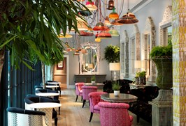 A row of small round tables with pink armchairs. The ceiling is lined with colourful basket pendant lights