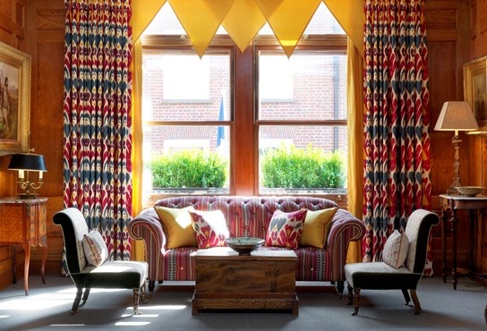 A sunny wood panelled drawing room with yellow curtains above a striped sofa