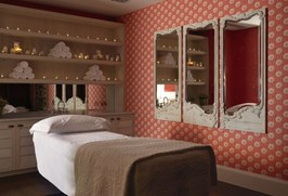 Spa treatment room with massage bed, on the bed is a white fluffy pillow and a blanket. On the right wall there is orange and white wallpaper. There are three framed mirrors hanging on the wall. On the back wall in the middle there are shelves with fresh white towels and Rik Rak products.