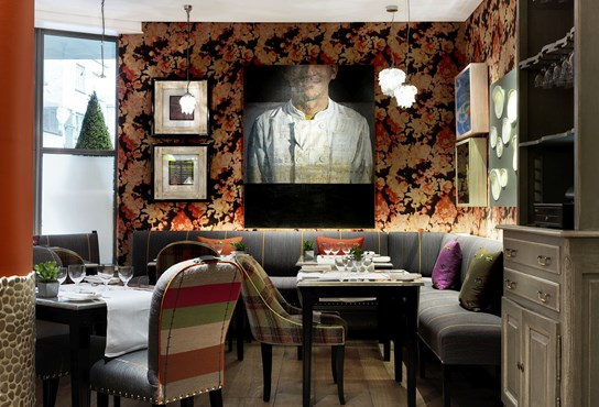 A photograph of refuel restaurant. Table covered in white table cloths surrounded by grey bench seating. The walls are clad in an orange floral wall paper. There is a painting of a chef on the wall.