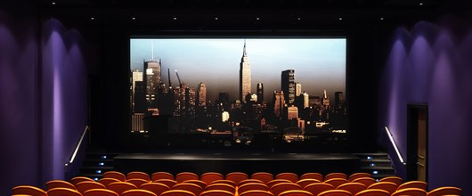 The screening room at the Crosby Street Hotel has 99 red leather seats by the Italia furniture company Poltrona Frau. There is a stage and wide screen here pictured with an image of the New York skyline.