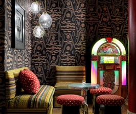 Soho Hotel Crimson Bar with a black patterned wallpaper, yellow stripe sofas and a bright neon Jukebox.